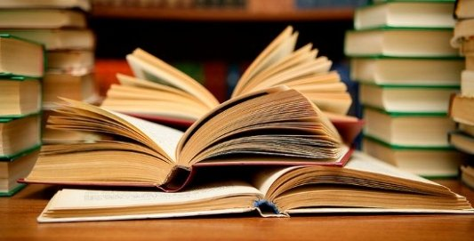Varios libros de colores abiertos sobre la mesa de una biblioteca