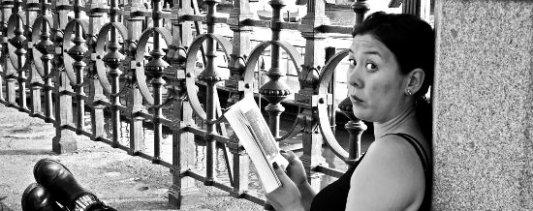Mujer sorprendida, leyendo un libro, tumbada al sol en un puente