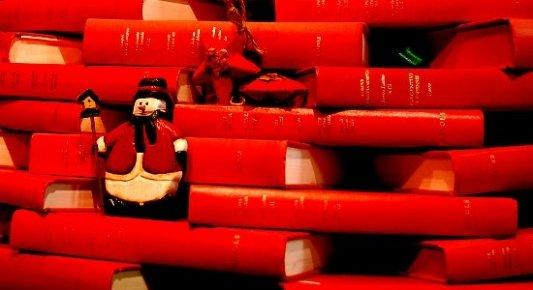Libros formando un árbol de navidad con adornos de hombre de nieve