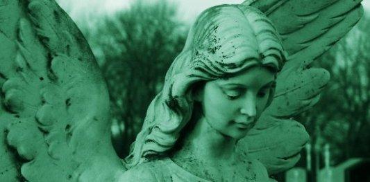 Escultura de un ángel triste de color verde en un cementerio