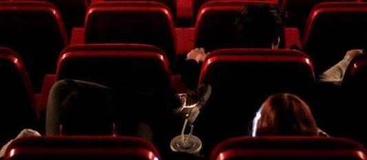 Sala de cine moderna en penumbra con butacas rojas y público