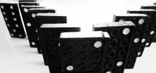 Fila de fichas de dominó negras y blancas dispuestas en V a punto de caer