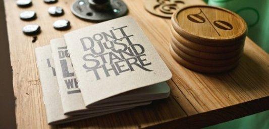 Mesa de imprenta tradicional con libros independientes y mensaje de ánimos