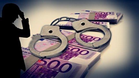 Silueta frente a fajos de billestes de 500 euros y unas esposas