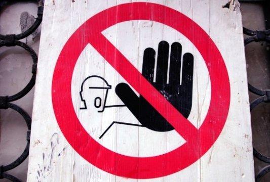 Cartel de Stop con figura de hombre levantando la palma de la mano