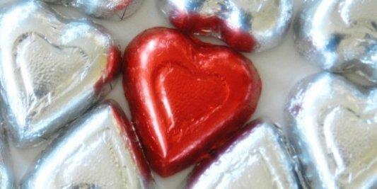 Grupo de corazones metálicos plateados con uno rojo en el medio