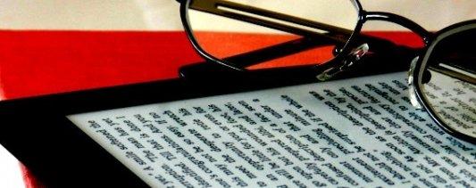 Primer plano de un ereader con un libro debajo y unas gafas encima