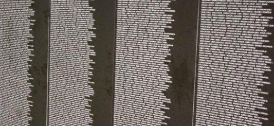 Vista parcial de un lista inscrita en un muro de color marrón