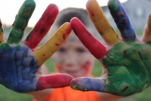Niño con las manos manchadas de pintura mirando a la cámara.