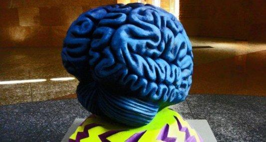 Cerebro gigante pintado de azul sobre una base de rayos