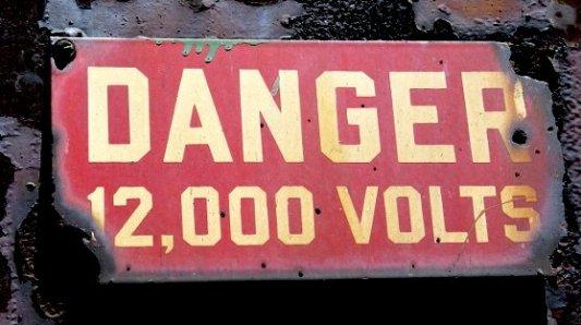 Cartel de peligro por electricidad bastante desgastado y oxidado.