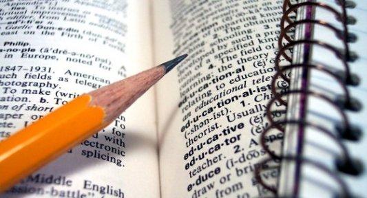 Libro de educación abierto por la mitad con un lápiz naranja señalando una frase