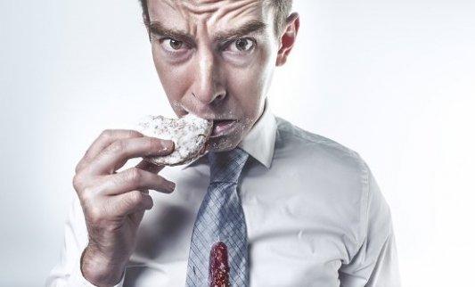 Hombre con la corbata manchada al comerse una galleta.