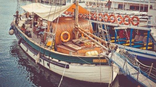 Espléndido barco de vela hecho de madera amarrado a puerto.