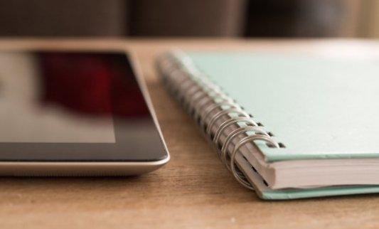 ipad y cuaderno situados juntos sobre una mesa de madera