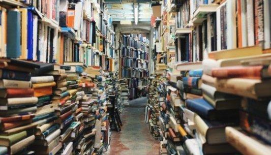 Libros de segunda mano apilados en una librería de lance.