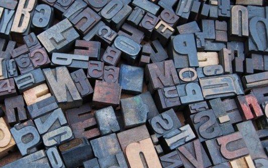 Decenas de fuentes tipográficas de hierro en una mesa de madera