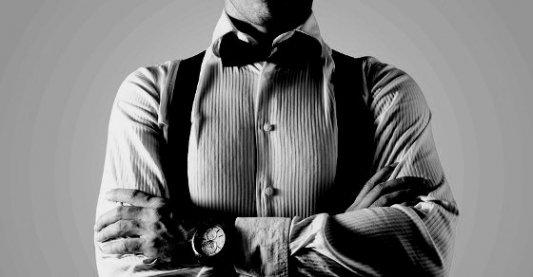 Imagen de un caballero con pajarita, camisa y reloj, posiblemente un espía.