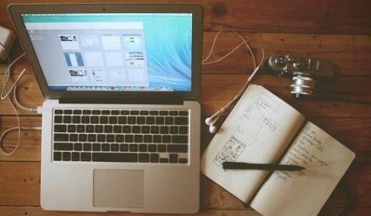 Ordenador apple imac sobre mesa de madera junto a cámara de fotos y cuaderno