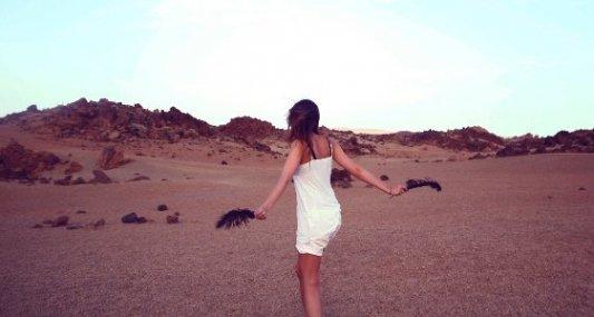 Joven mujer en medio del desierto bailando con dos plumas.