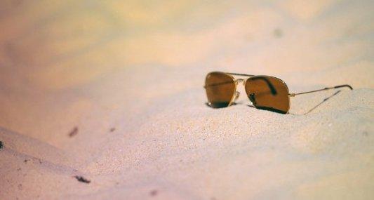 Gafas estilo aviador abandonadas sobre la arena de la playa en pleno verano.