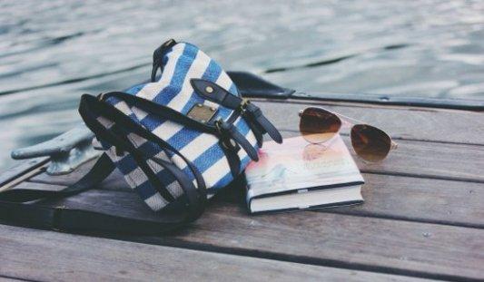 Bolso, libro y gafas de sol apoyadas en un muelle junto al mar.