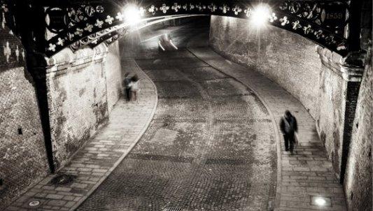 Imagen nocturna de un joven paseando bajo un puente modernista.