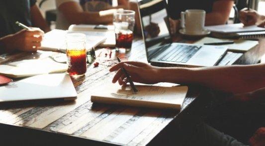 Varios escritores con ordenadores y libretas de reunión.