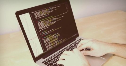 Persona programando código en un ordenador portátil.