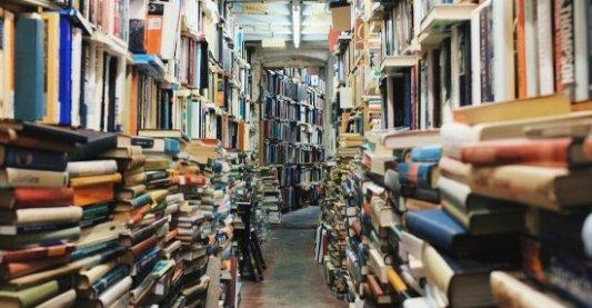 Librería con cientos de libros apilados en las paredes.