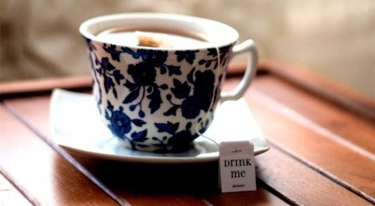 Taza de té recién hecho con la leyenda de Drink Me en un lateral de la bolsa de té.