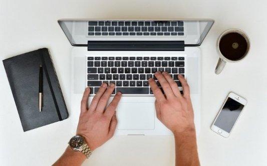 Escritor con un ordenador portátil, teléfono y taza de café.
