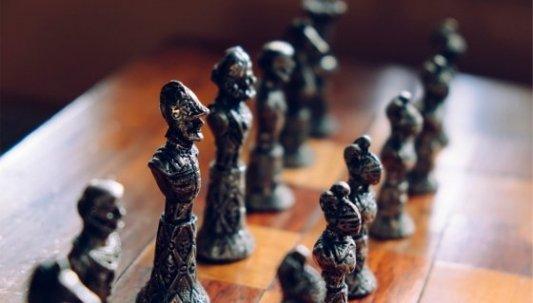 Tablero de ajedrez con piezas de metal que parecen soldados.