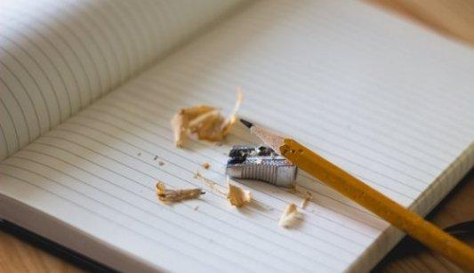 Papel, lápiz, sacapuntas y cuaderno en blanco para escribir.