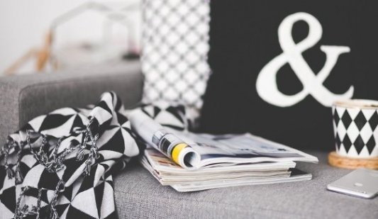 Sofá de diseño con letras, revistas, taza de té y teléfono móvil.
