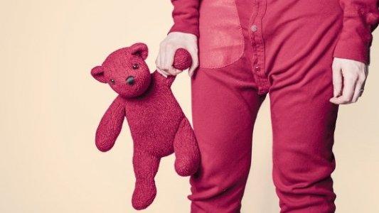 Niño con pijama rojo llevando de la mano a un oso de peluche.
