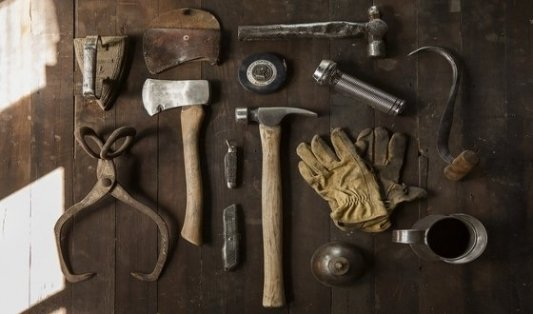Completo juego de herramientas algo oxidadas sobre vieja mesa de madera