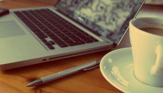 Ordenador portátil sobre la mesa junto a un bolígrafo y una taza de café