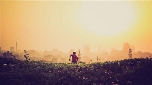 Joven indio corriendo por una colina con una ciudad al fondo