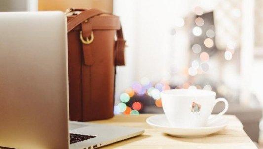Ordenador portátil sobre una mesa, junto a una taza de café y una bolsa de cuero.