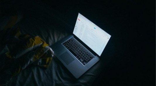 Ordendor portátil sobre una cama en una habitación oscura.