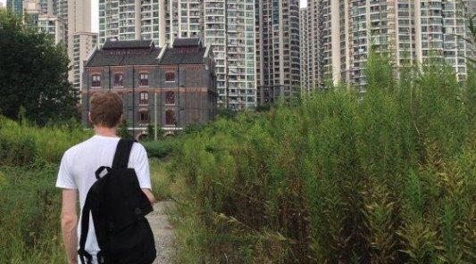 Joven con una mochila frente a una misteriosa casa en medio de la ciudad abandonada.