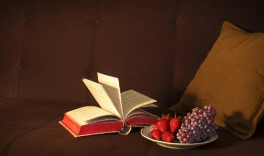 Fotografía de bodegón que incluye un libro antiguo abierto por la mitad.