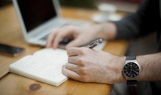 Imagen de un escritor tomando notas en una libreta junto al ordenador.