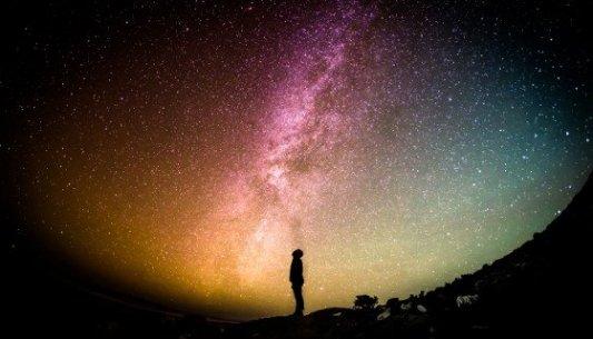 Persona en mitad de la noche a contraluz de una galaxia llena de estrellas.