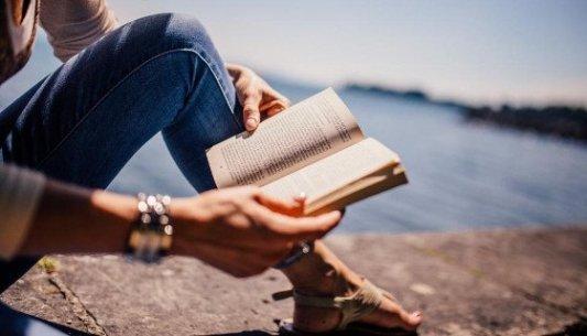 Chica leyendo un libro sobre un pretil de piedra junto al mar, sentada en el suelo.