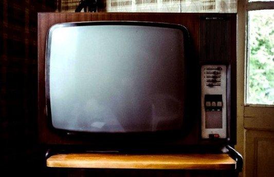 Vieja televisión sobre una mesa de madera con los controles estropeados.