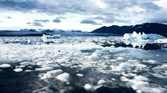 Paisaje ártico lleno de icebergs, lago helado donde predomina el blanco y el azul.