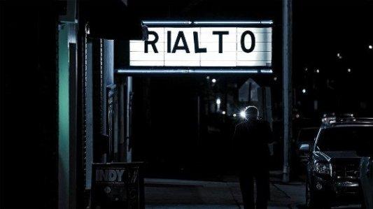 Cartel del cine Rialto de noche en una escena tomada a contraluz.