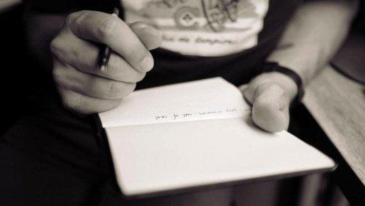 Escritor con una libreta abierta donde está tomando notas con un bolígrafo.